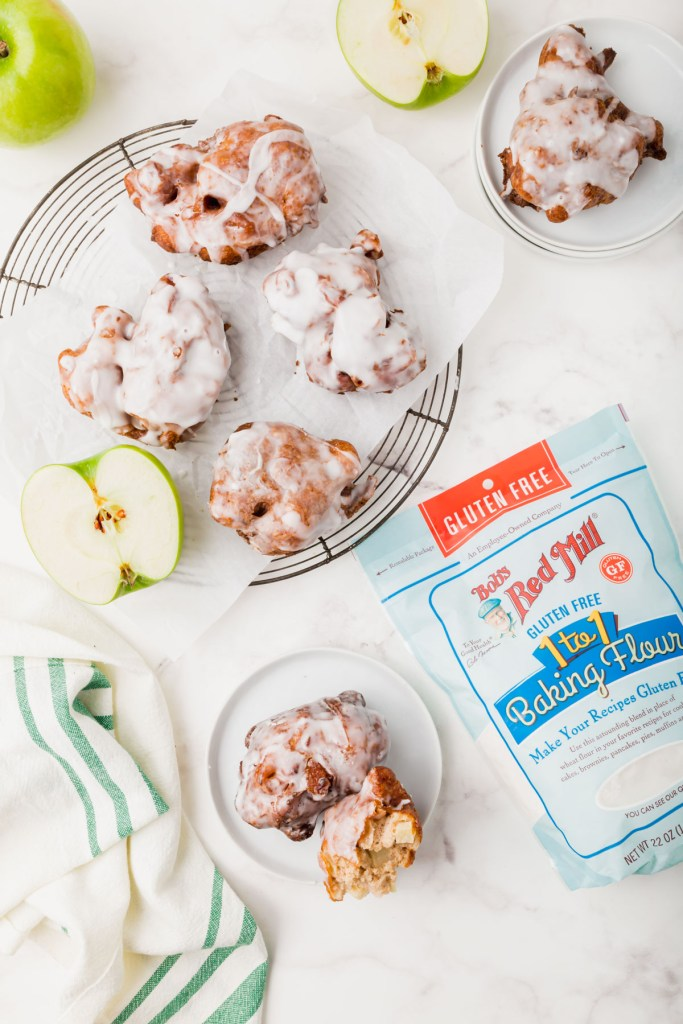 gluten-free apple fritters on a cooling rack with Bob's Red Mill gluten-free flour bag