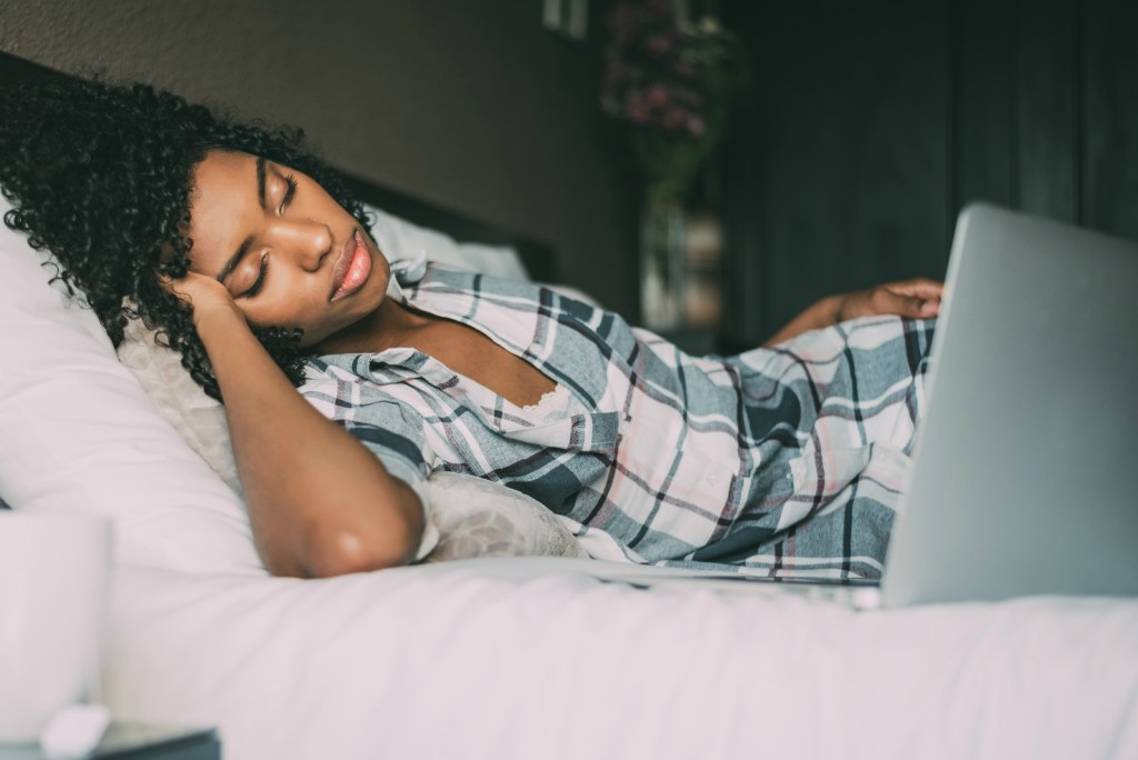 beautiful black woman on bed with laptop sleeping