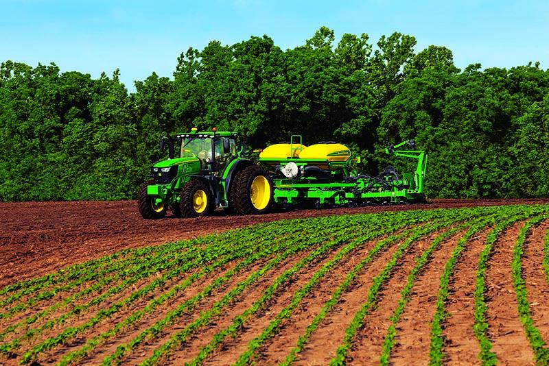 A John Deere tractor pulling a sprayer in a field of soybeans