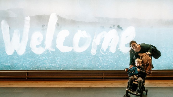 Mom and toddler near welcome sign in Keflavik Airport Iceland