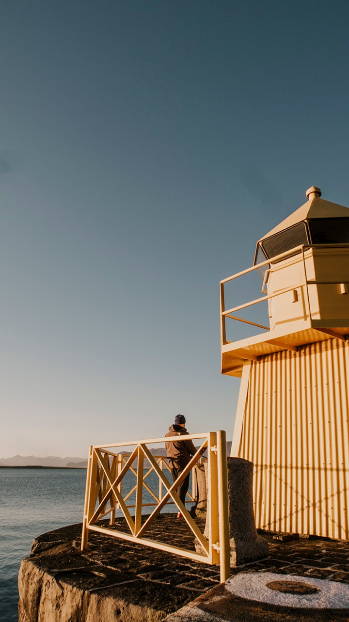 A yellow lighthouse with a man fishing at the Reykjavik harbor in Iceland