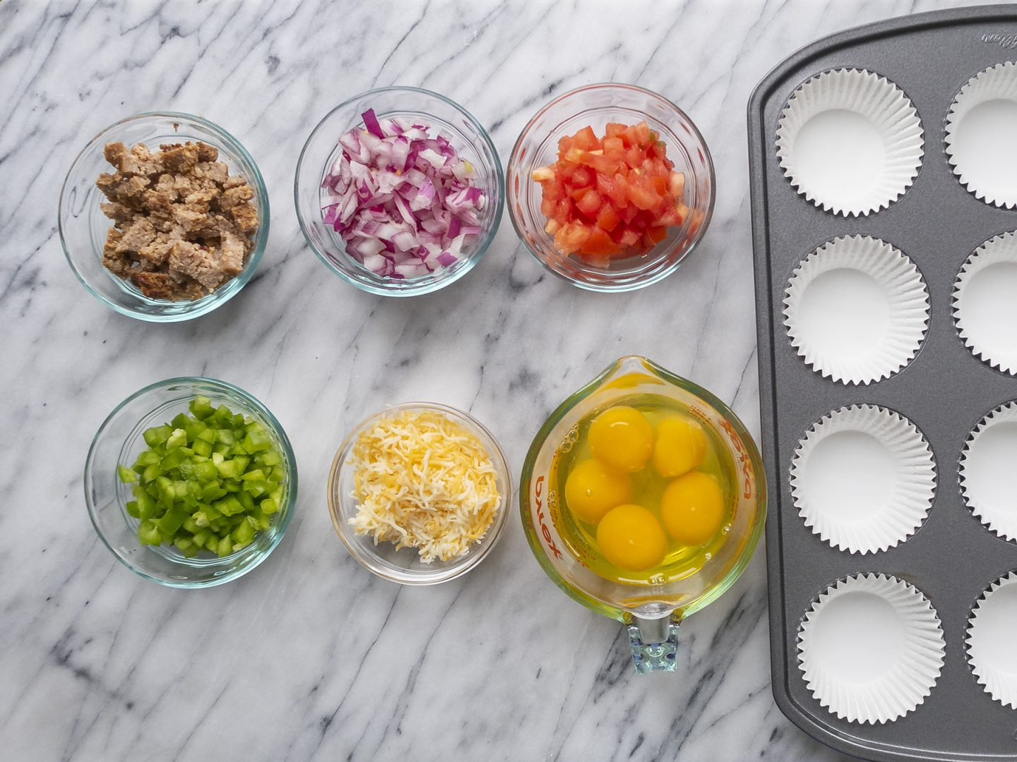 Ingredients to make sausage, veggies and cheese breakfast egg muffins