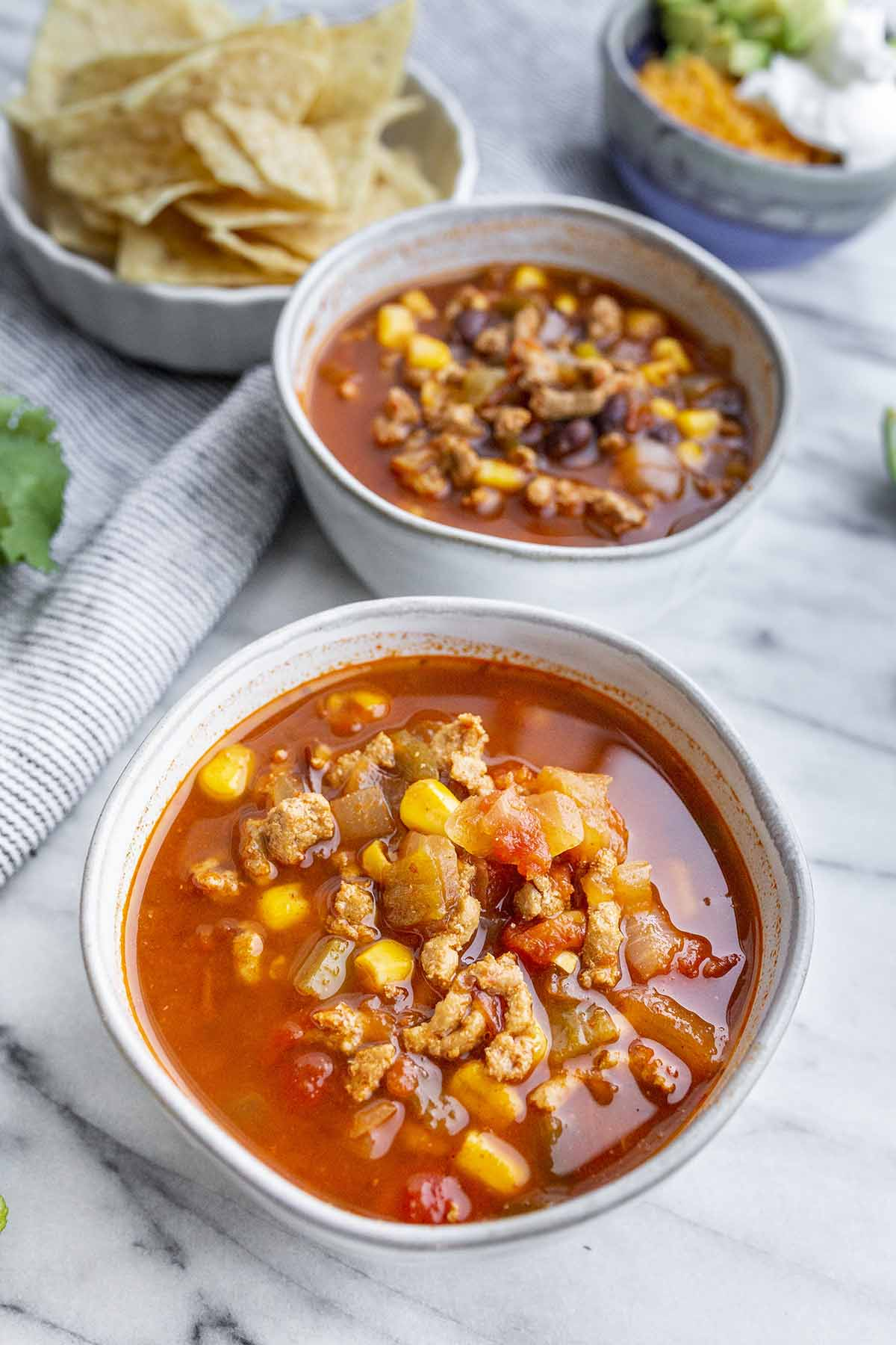 Broth Turkey Taco Soup Recipe served with tortilla chips, avocado, cheese and sour cream