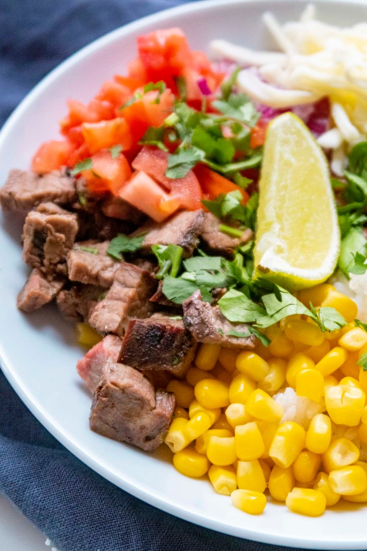 Homemade Burrito Bowl with carne asada, tomatoes, corn, cheese and lime