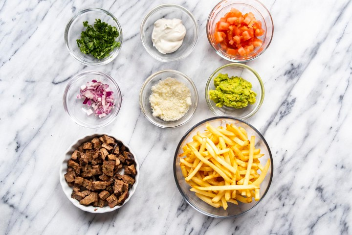Ingredients to make carne asada fries - diced beef, french fries, guacamole, cheese, onions, tomatoes, cilantro and sour cream
