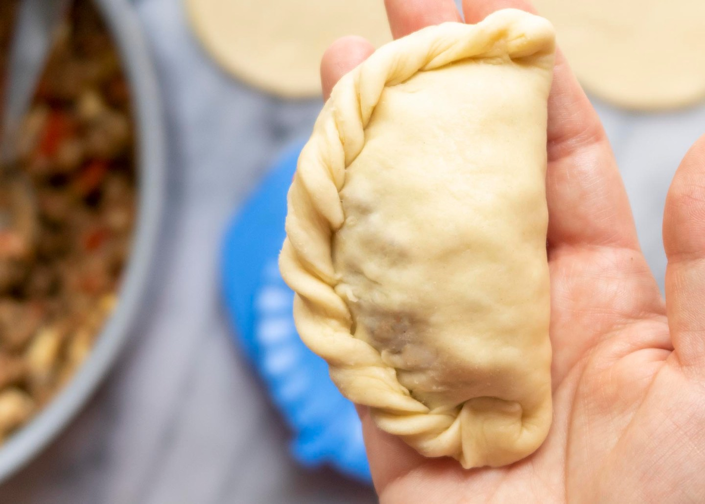 The roped edge of an unbaked Empanada