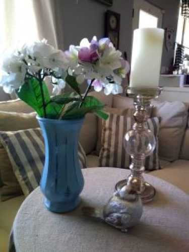 Picture of a vase. candle stick holder and a silver bird