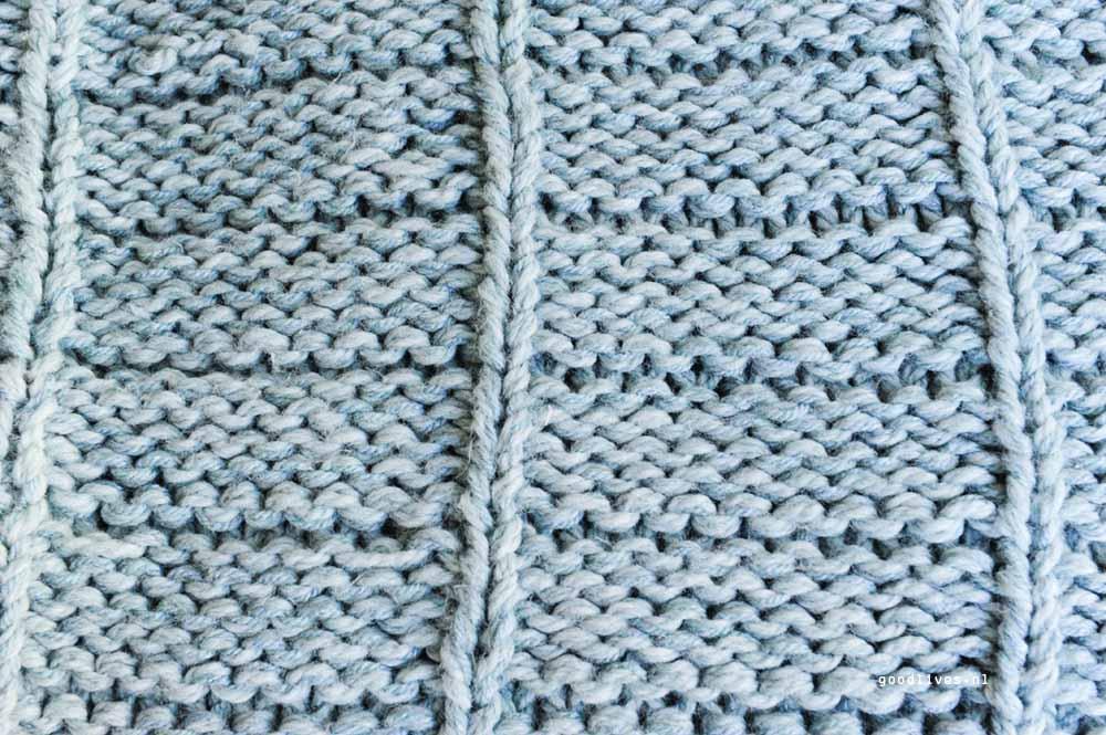 De achterkant van het DIY patroon van een warme plaid