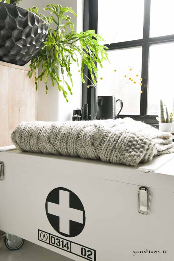 Beige DIY knitted cable blanket on wooden box