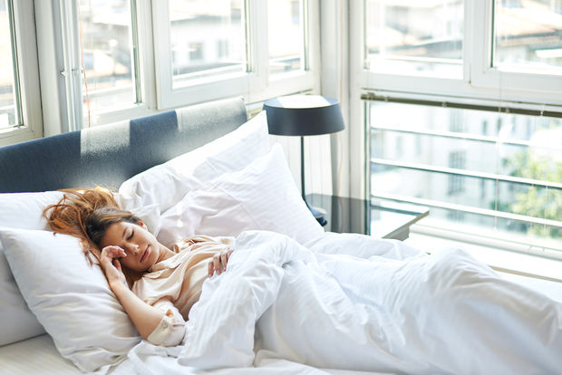 A woman is sleeping in a luxurious and comfortable bed. (Shutterstock)