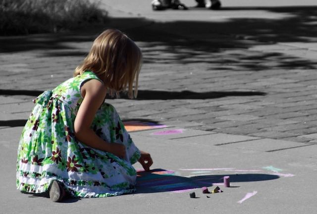 Girl drawing on the street with chalk