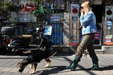 Woman walking dog and smoking