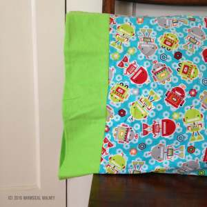 Flannel pillowcase with colorful, happy robots.