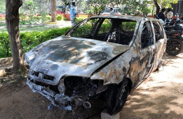 Indian pedestrians gather near the burnt-out shell of a vehicle which was set ablaze by a mob at a local police station in Bangalore, southern India on February 2, 2016