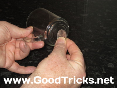 Image showing coin being tapped on base of glass to prove that it is solid.