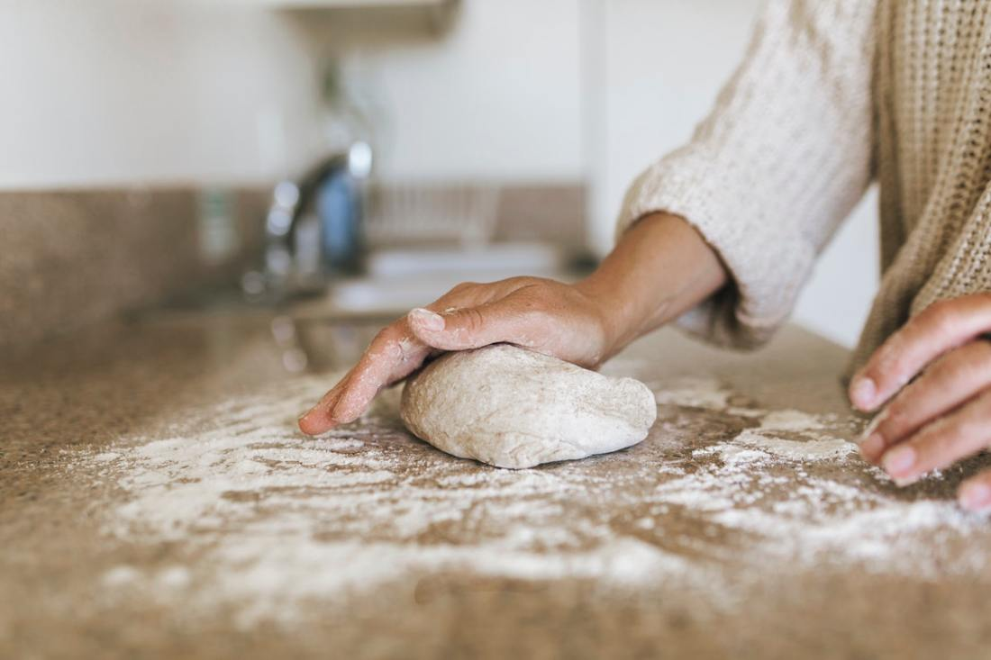 Woman kneading a sourdough in her kitchen