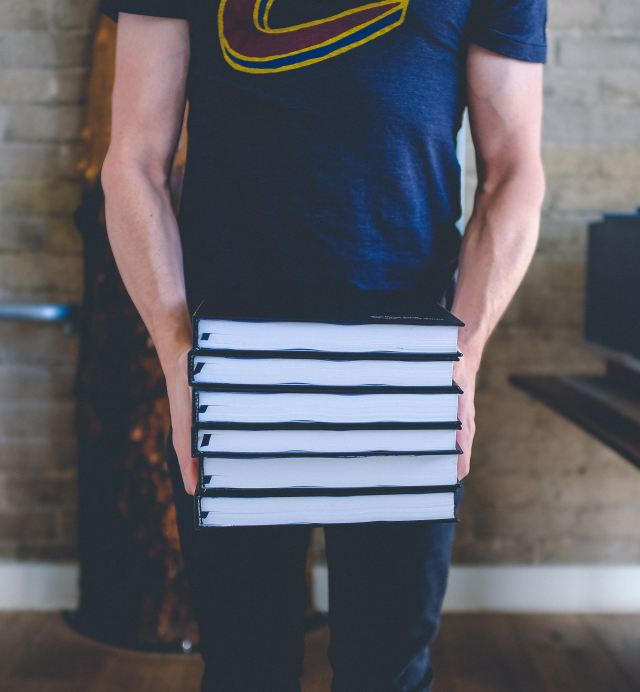 man carrying stacks of books