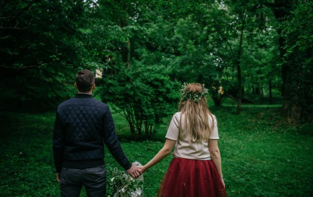 couple holding hands in green space