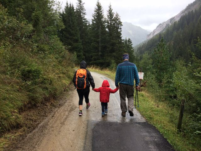 Family walking down road hand-in-hand