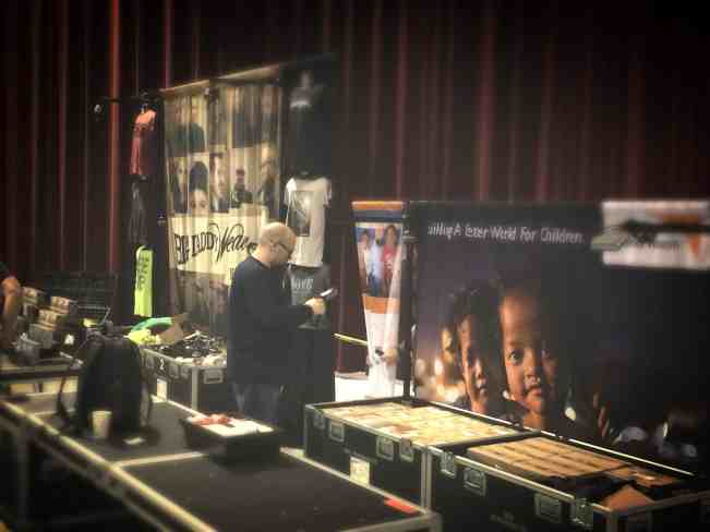 Jay sets up the World Vision display beside Big Daddy Weave's merch table.