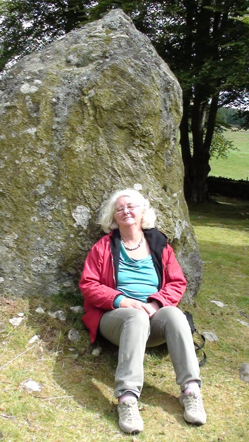 Relaxing by a standing stone at the Clava Cairns.