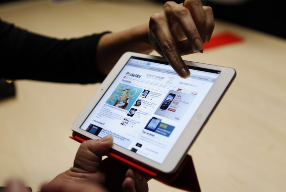 Visitors look over the new iPad mini at an Apple event in San Jose