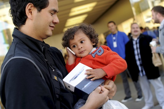 Kai Lanier plays with his dad's newly purchased iPhone 5 outside an Apple Store in San Francisco