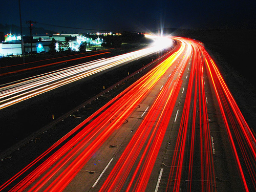 An example of light trail photography showing cars' headlights and tail lights on a busy highway. Image via digital-photography-school.com