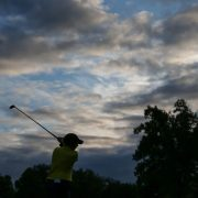 Image of woman golfer at twilight.