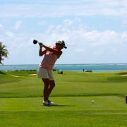 Image of woman teeing off from reds
