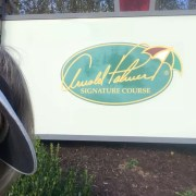 Lin peeking out from Arnold Palmer sign