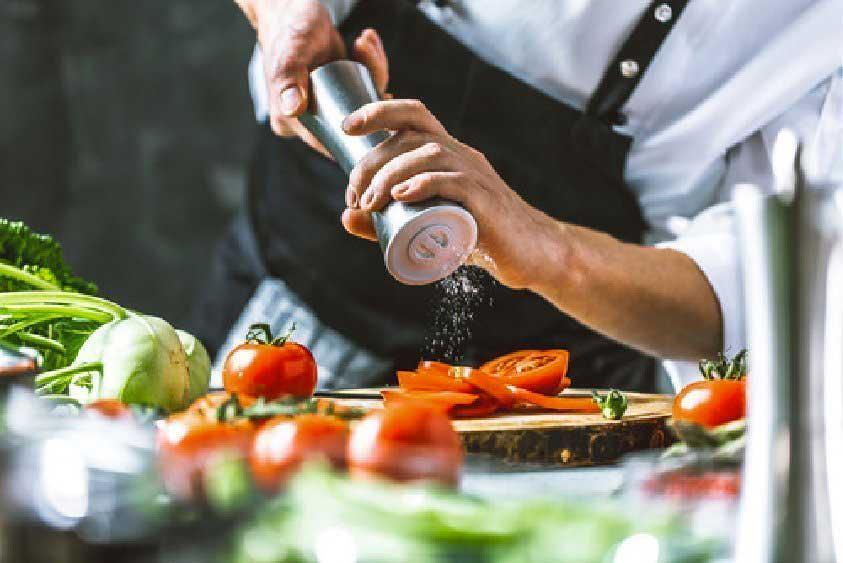 Cuisinier en train de saler des tomates