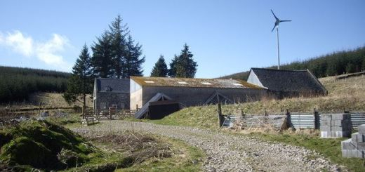 Farm buildings with small wind turbine behind