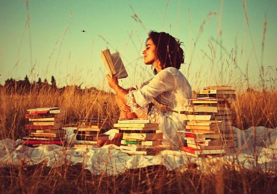 Imagem colorida com filtro. Mulher de de cabelo médio e castanho, vestindo vestido branco lê um livro sentada sobre um tecido branco em um campo aberto com vegetação amarelo-palha. Existem cinco pilhas de livros ao seu redor.