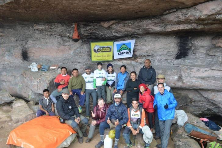 O grupo está embaixo de um teto rochoso e à frente de uma parede rochosa onde estão penduradas as bandeiras do GPM e do Roraima Adventure