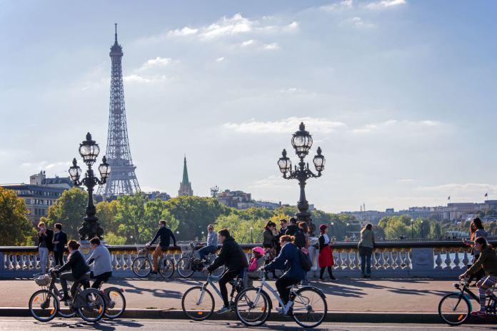 Des personnes font du vélo à Paris par beau temps