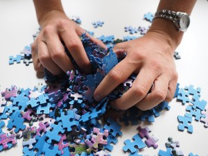 hands picking up puzzle pieces