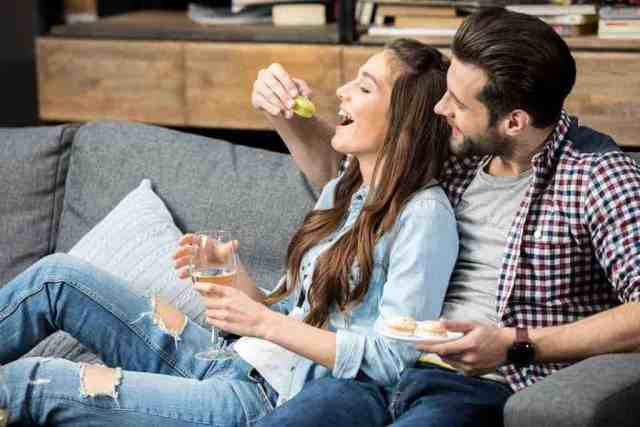 at home date night couple laughing and eating on the couch