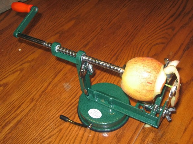 Apple being peeled by a corer, peeler, slicer.