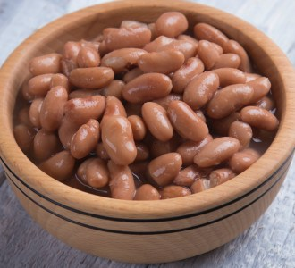 A brown bowl of cooked pinto beans.