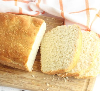 Homemade English Muffin Bread sliced on a wooden cutting board.