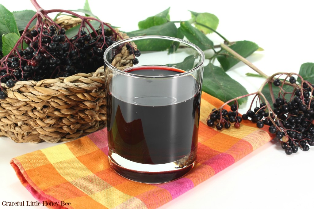 Elderberry juice with elder berries and leaves on a white background.