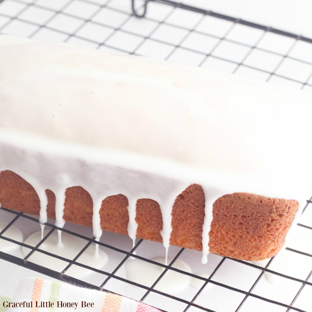 Finished pound cake drizzled with glaze on a cooling rack.