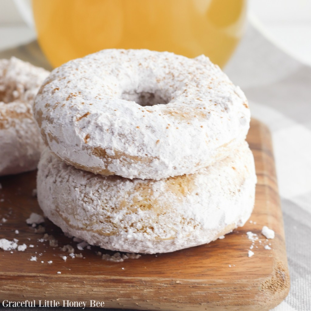 Two Apple Cider Donuts stacked on a wooden cutting board with a glass of apple cider in the background.
