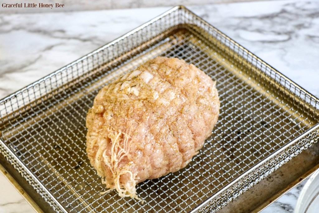 Raw turkey breast sitting in air fryer basket.