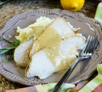 Sliced turkey breast on a gray plate topped with gravy and garnished with fresh rosemary and lemon slices.