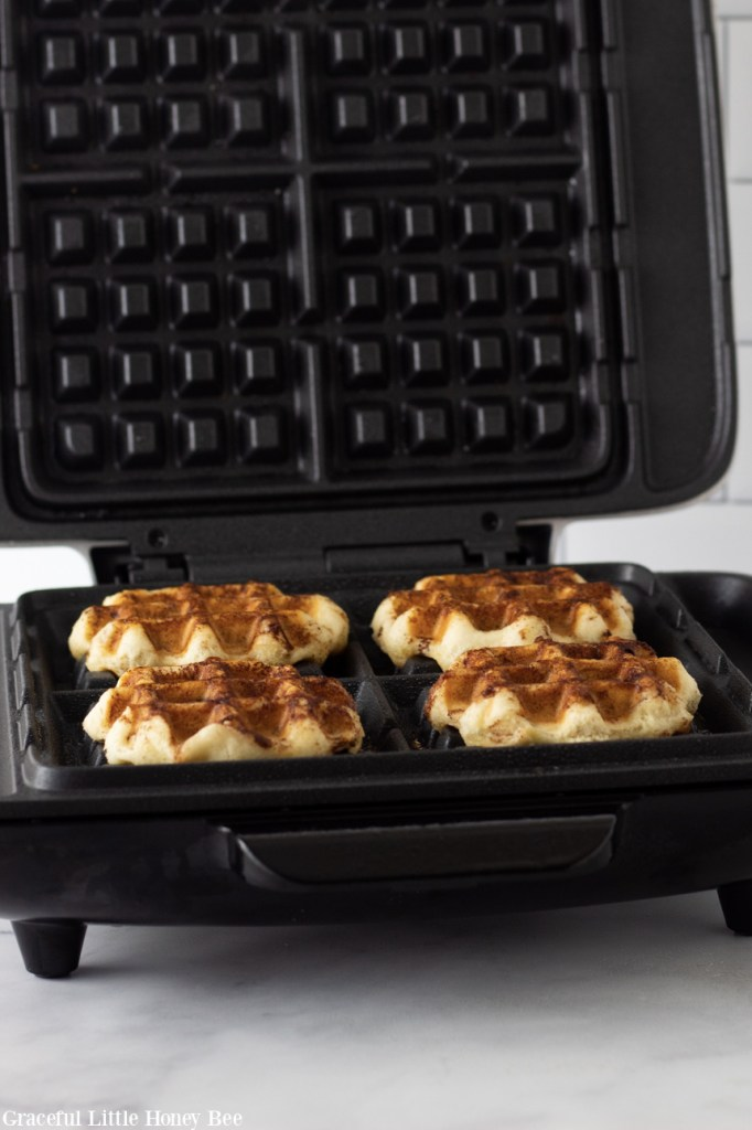 Crispy cinnamon roll waffles in the waffle iron.