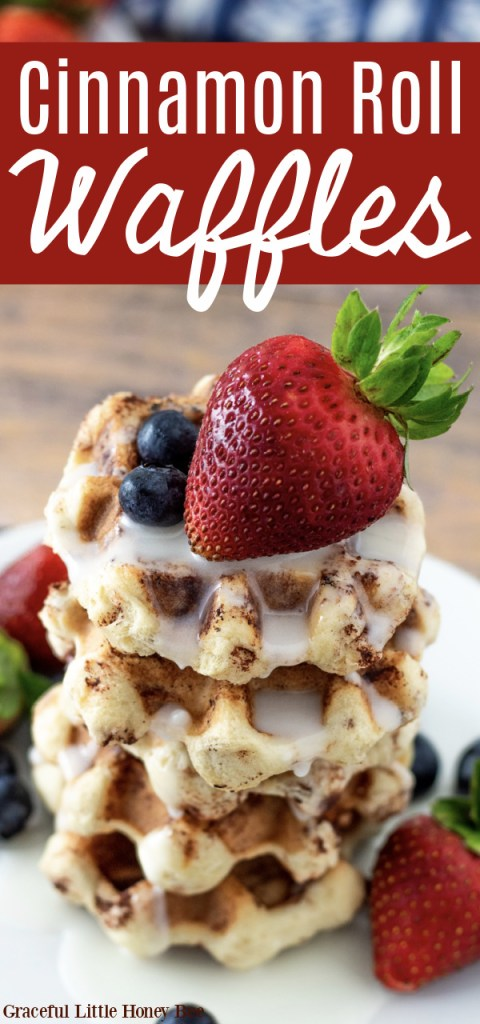 Cinnamon Roll Waffles stacked on a plate drizzled with glaze and topped with fresh fruit.