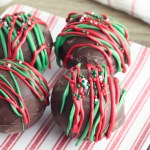 Four hot chocolate bombs sitting on a red and white striped plate.