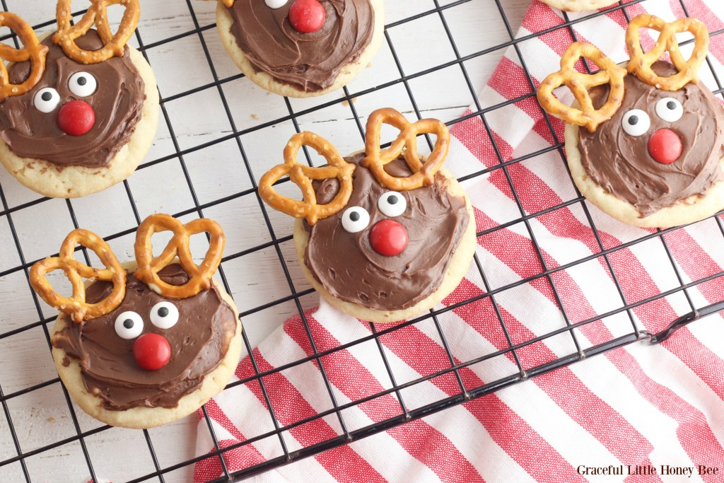 Finished reindeer cookies sitting on a black wire cooking rack with a red and white checked towel underneath.